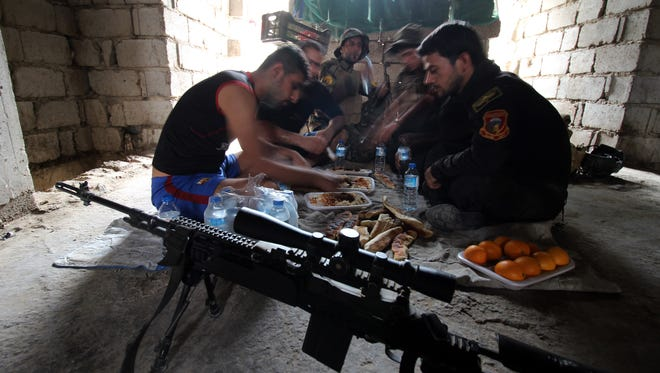 Members of a counter-terrorism unit have lunch as they hold a position in the Al-Hayakel area on the eastern outskirts of Fallujah during a military operation conducted by Iraqi government forces and Popular Mobilisation units against Islamic State group jihadists on September 10, 2015.