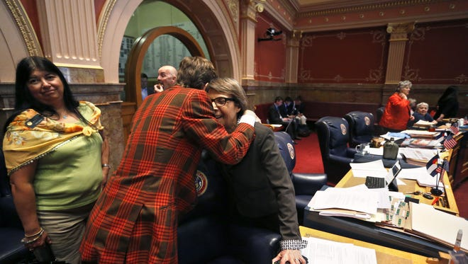 Democratic state Sen. Mike Johnston, center, hugs fellow Sen. Lucia Guzman on the closing day of the 2015 Colorado legislative session. Guzman, the Senate minority leader, expects the 2016 session to be fraught with fights on social issues and pre-election posturing.