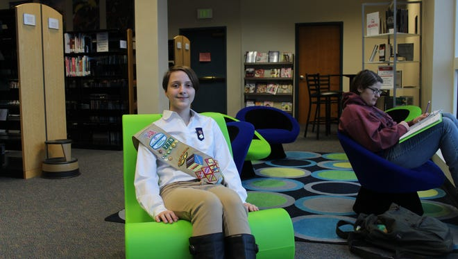 Ava Ploeckelman, 14, of Northeast High School, sits in one of the chairs she raised money for as part of her Girl Scout Silver Award project.