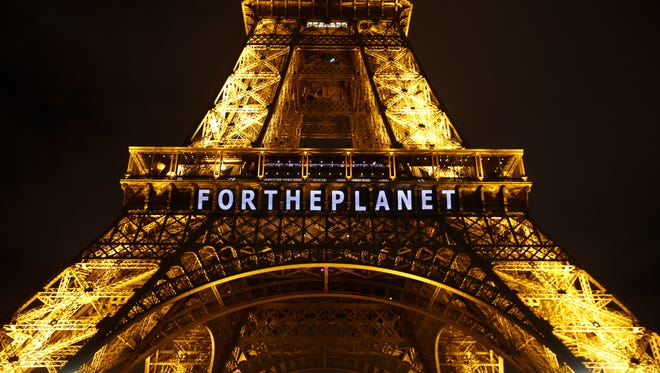 """The slogan """"FOR THE PLANET"""" is projected on the Eiffel Tower as part of the COP21, the United Nations Climate Change Conference in Paris on Dec. 11, 2015."""