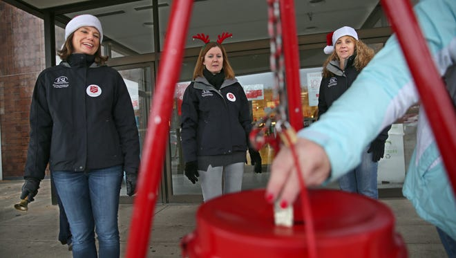 From left, ESL Federal Credit Union workers Yvette Charleton, Julie Demo and Gail Percey volunteer as Salvation Army bell ringers outside Macy's at Eastview Mall in Victor on Tuesday.