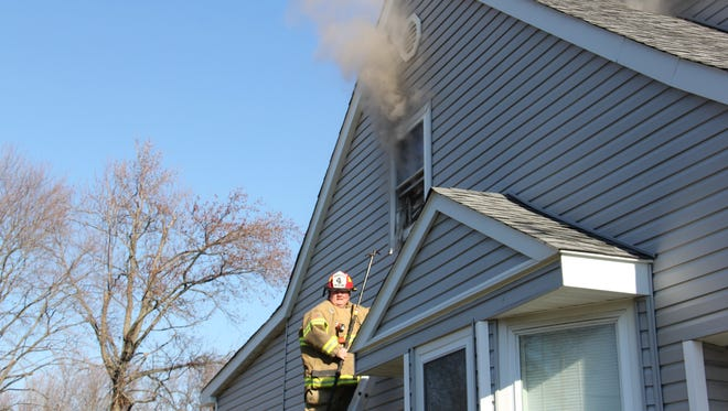 A Middletown Township firefighter working to contain a blaze on the second floor of a home on Route 36 on Saturday.
