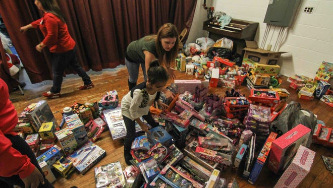 Volunteers Kandra Dickerson and Savannah Dipres (8) retrieves toys during the fourth Annual West Side Neighborhood Coalition christmas dinner and toy giveaway Monday, Dec. 21, 2015 at St Paul's Catholic Church in Wilmington.