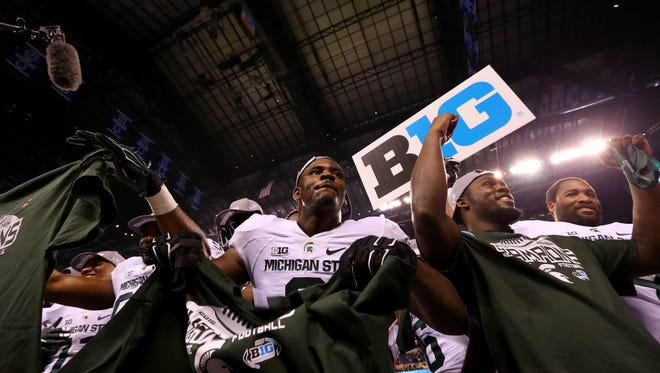 Michigan State defensive lineman Lawrence Thomas (8) holds up his Big Ten Championship T-shirt after defeating Iowa in the Big Ten Championship Game at Lucas Oil Stadium on Dec. 5, 2015.