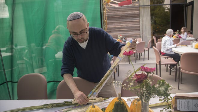 Rabbi Steven Edelman-Blank prepares the lulav and etrog inside the sukkah during the holiday celebration for Sukkot at Tifereth Israel Synagogue in Des Moines, Iowa, Sunday, Oct. 4, 2015.