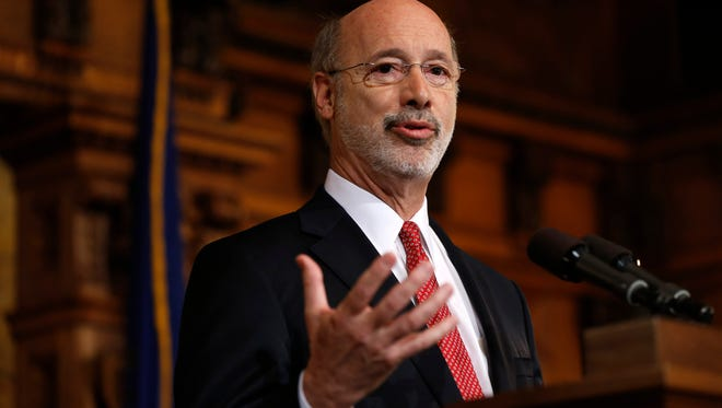 Pennsylvania Gov. Tom Wolf speaks with members of the media Tuesday, Dec. 29, 2015, at the state Capitol in Harrisburg, Pa. Wolf says he is rejecting parts of a $30.3 billion state budget plan that's already a record six months overdue, but he's freeing up over $23 billion in emergency funding.