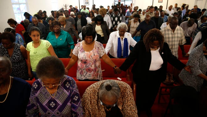 Community members hold hands in prayer at St. Paul AME Church in Blountstown on Monday. The news conference, which sounded more like a Sunday sermon, was to bring people together in the wake of 57-year-old Barbara Dawson's death on Dec. 21.