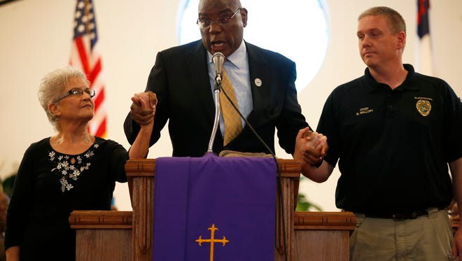 Rev. R.B. Holmes Jr., center, holds up the hands of Calhoun Liberty Hospital Chief Administrator and CEO Ruth Attaway and Blountstown Police Department Chief Mark Mallory as they announce a claim of solidarity for transperacy in searching for the causes behind the death of Barbara Dawson, who died the morning of Dec. 21 after she was arrested at the Calhoun Liberty Hospital where she had gone for treatment.Officials and church leaders gathered together Monday at St. Paul AME Church in Blountstown for the press conference.