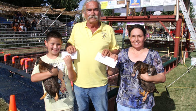 Duck Wrangler Steve Smith, center, presents checks in the amount of $1,345 to each winner of the 36th annual Great American Duck Race; Jace Moreno, 9, and Mary Zischkau.