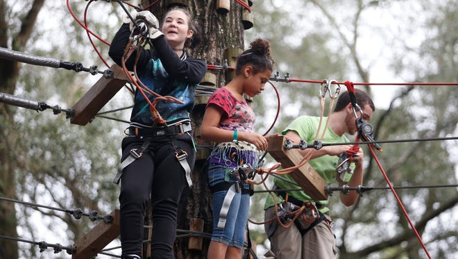 Neena Maddox, 14, left, and Jacelyn Arceneaux, 11, take to the zip line coarse during an outing for the children from Boys Town North Florida at the Tallahassee Museum.