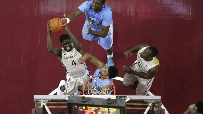 FSU's Dwayne Bacon grabs a rebound over North Carolina's Marcus Paige (5) and Joel James (42) during the Tar heels' 106-90 win at the Tucker Center on Monday, Jan. 4, 2016.