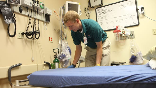 CSU volunteer Graham Gilliland makes up an ER bed during his weekly volunteer shift at Medical Center of the Rockies ER.