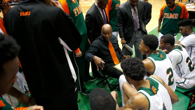 FAMU's Head Coach Byron Samuels talks to his team in a huddle during a timeout in their game against Savannah State defenders at the Lawson Center on Tuesday.