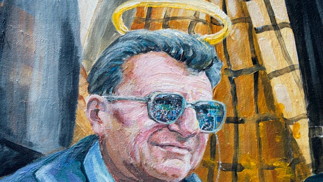 FILE - In this July 12, 2012, file photo, part of a mural showing former Penn State head football coach Joe Paterno is shown on a wall in downtown State College, Pa. A painted halo on a mural of former Penn State football coach Joe Paterno is back, more than three years after the artist removed it shortly after Jerry Sandusky was convicted of child molestation. (AP Photo/Gene J. Puskar, File)