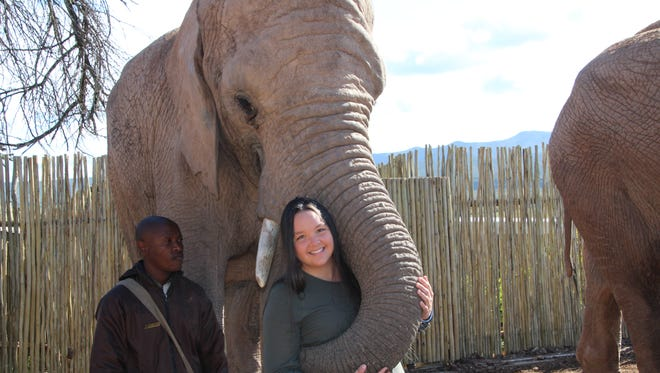 Katie Ommanney, a Delaware State University student, gets a trunk-hug from an elephant