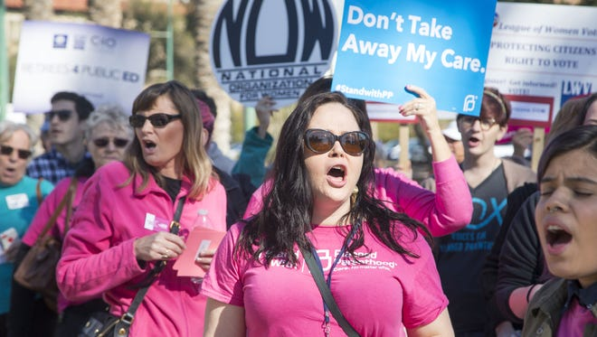 Protesters representing Planned Parenthood, ACLU, unions, Sierra Club rally at Wesley Bolin Plaza before Gov. Doug Ducey delivered his State of the State address in the House chambers on Jan. 11, 2016.