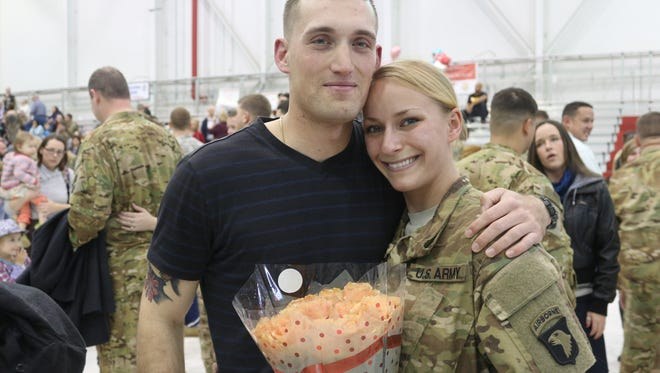Spc. Christian Claudio, left, proposed to his girlfriend Spc. Brittney Block as she was welcomed home with more than 250 other soldiers from Fort Campbell's 101st Combat Aviation Brigade on Friday.
