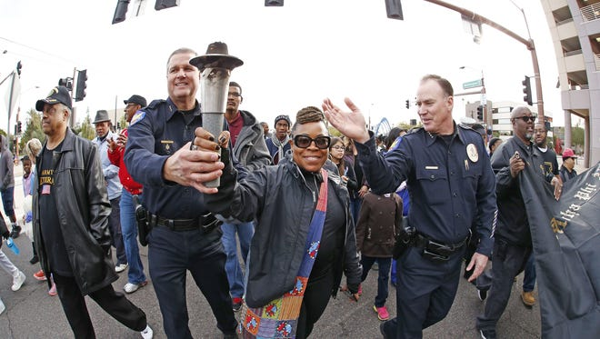 Phoenix Assistant Chief Michael Kurtenbach, Marchelle Franklin with City of Phoenix Police Community Affairs and Chief of Police Joseph Yahner (right) join several thousand people march in the MLK March Parade on Jan. 18, 2016 in Phoenix, Ariz. The march celebrates Martin Luther King, Jr., the slain civil-rights leader's life and the fight for equality.