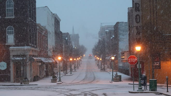 Snow falls in downtown Clarksville on Wednesday morning.