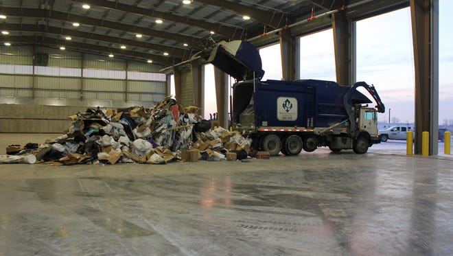 The first load of garbage is dumped at the Metro Waste Authority's new transfer station in Grimes, which opened Thursday.
