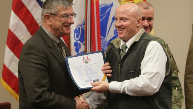 Sgt. 1st Class Michael Hall, right, accepts his certificate for completing the Veterans In Piping program from retired Maj. Gen Anders Aadland, a consultant with the United Association.