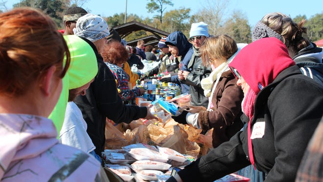 Hundreds of people traveled through the food line at the ReImagine Milton event Saturday and waited in line around Carprenter's Park on Munson Highway in order to receive free, healthy foods for their families.