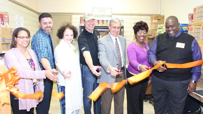 A School Pantry has been opened at Paul Breaux Middle. Pictured from left are Paul Breaux Vice Principal Lisa Semere, Paul Breaux Principal Stephen Judice, Second Harvest President/CEO Natalie Jayroe, Billy Mick of Raising Cane's, Lafayette Parish Superintendent Donald Aguillard, Pantry Coordinator Crystal Bowie and Lafayette City-Parish Councilman Kenneth Boudreaux.