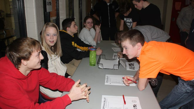 Students fill out ballots and ask questions with the poll workers during the straw poll Thursday, Jan. 28, at Williamsburg High School.