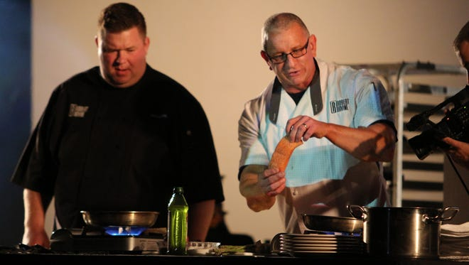 Chef Robert Irvine cooks salmon during Friday night's show at Fort Campbell's Wilson Theater.