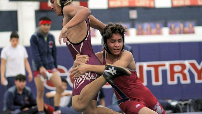 Deming's Lorenzo Madrid, right, had a tough time with an elusive Rigoberto Camera of Gadsden high School in their match at 113 pounds. Madrid eventually came away with a victory by fall 55 seconds into the second period. Deming hosted and defeated the Gadsden Panthers in District 3-6A dual wrestling 61-24.