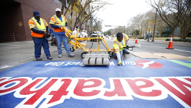 Clarence Johnson, right, puts the finishing touches on a permanent finish line for the Tallahassee Marathon, molded to Duval Street downtown Sunday. The new route of the Tallahassee Marathon, which takes place this weekend, will conclude at the intersection of South Duval Street and West Jefferson Street.