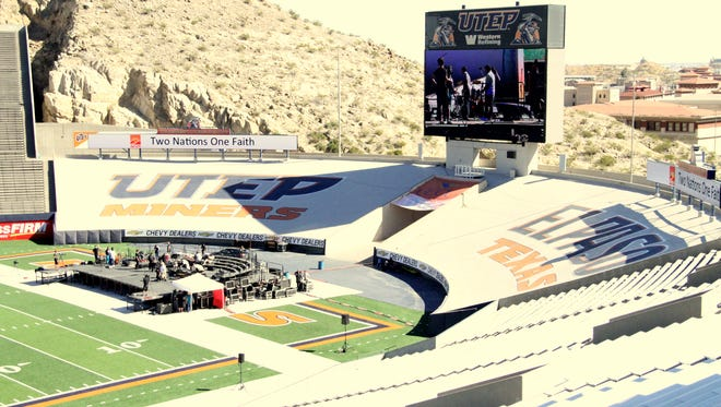 Crew members set up the stage for pope festivities Monday afternoon at the Sun Bowl.