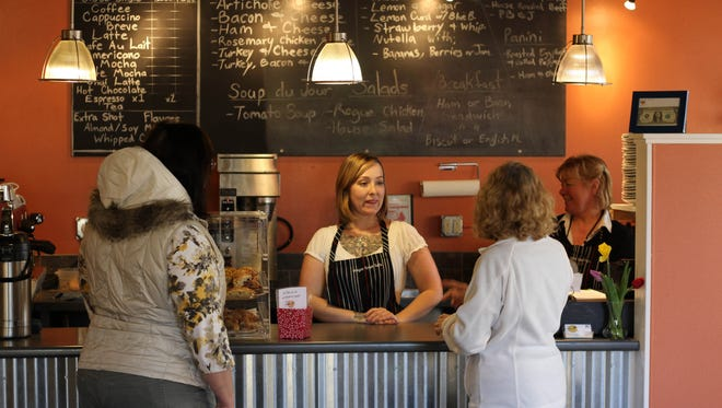 Danielle Baca, center, helps customers at Oregon Crepe Cafe & Bakery in Pringle Plaza last year when it opened. The restaurant is celebrating its first anniversary in the location.