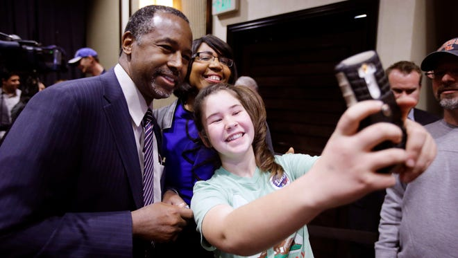 Ben Carson, and his wife, Candy, pose for a selfie with a young supporter after a town hall meeting on Feb. 21, 2016, in Reno, Nev.