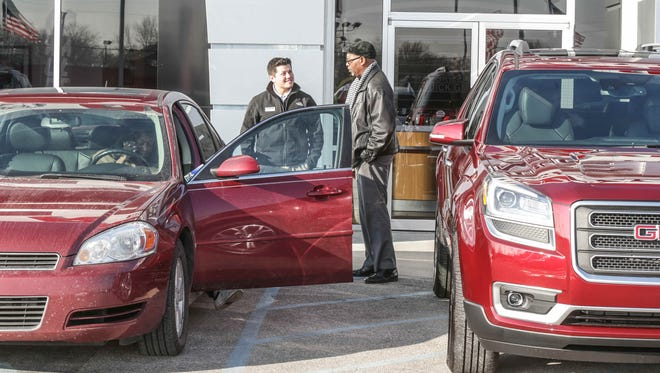 Ray Skillman's Jesus Angeles, center, spoke with customer Lacy Boyd, right, while his wife, Donella Boyd, transferred possessions from their trade-in car to their new GMC Acadia on Feb. 16, 2016, at Ray Skillman Northeast Buick GMC.