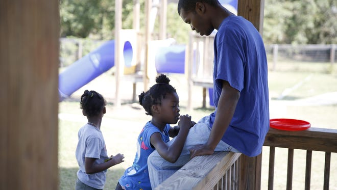 Michael Byrd Jr. shares a moment with his daughter Mo, 8, at the playground of the HOPE Community, a transitional housing program managed by the Big Bend Homeless Coalition. Byrd, a single parent, has sole custody of his five children and the family currently resides at the facility.