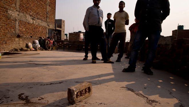 Relatives stand on the terrace of a house where a 15-year-old girl was set on fire after being raped at Tigri village, near Noida, a suburb of New Delhi, India, Tuesday, March 8, 2016.