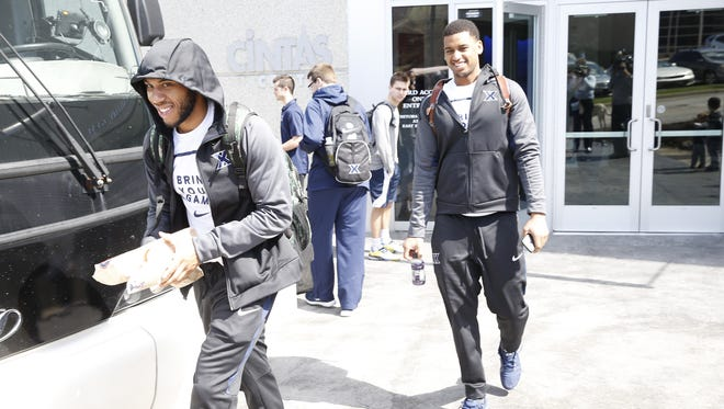 Myles Davis (left) and Trevon Bluiett board the Xavier bus Wednesday at Cintas Center before heading to the airport and flying to Saint Louis for the  NCAA tournament.