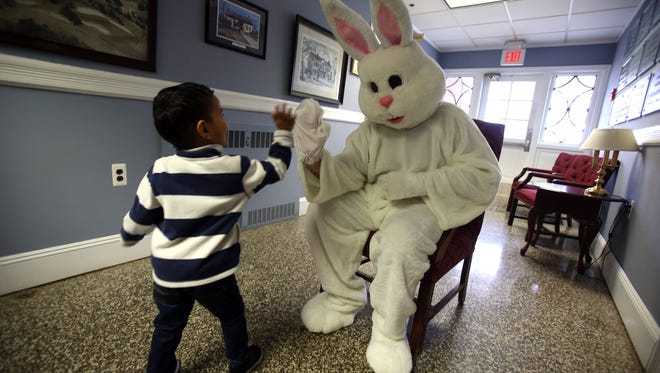 3-year-old Garvit Upadhyay of Lake Hiawatha gives the Easter bunny a high-five at the Township of Parsippany-Troy Hills hosts a visit from the Bunny at the Parsippany Municipal Building for children of all ages. March 19, 2016. Morristown, N.J.