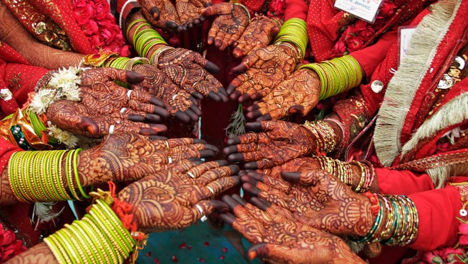 Indian brides display henna designs on their hands as they pose for a photograph during a mass marriage for 41 couples in Ahmadabad, India, on  Nov. 20, 2011.