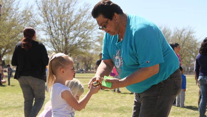 Bella Briscoe, 5, hands Mario Carrasco, career services coordinator at New Mexico State University Carlsbad her golden egg in exchange for free movie passes at the Golden Egg Hunt Saturday morning.