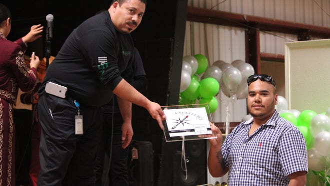 Patricio Fierro, right, was the recipient of Mizkan America Inc. Award of Excellence. The green chile food manufacturing plant in Deming selected Fierro as one of its top employees. The award presentation took place this past Thursday during an employee appreciation dinner to announce the integration of two of Mizkan's top companies. Presenting the award was Manuel Hernandez at left.