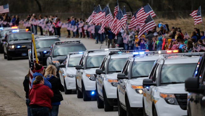 Students from Van Meter line the road to watch as the funeral procession for Des Moines Police Officer Carlos Puente-Morales arrives in Van Meter Friday, April 1, 2016.