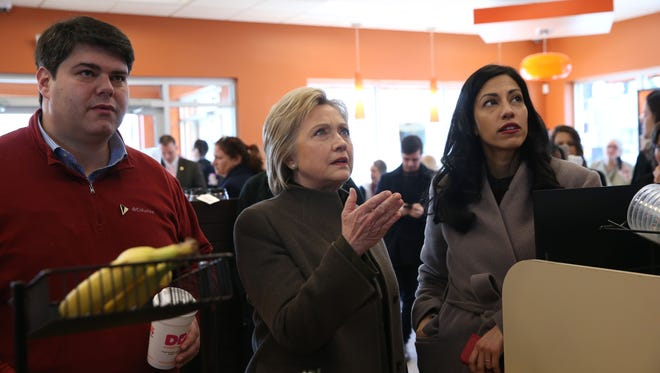 Hillary Clinton prepares to order at a Dunkin Donuts with New Hampshire state campaign director Mike Vlacich and aide Huma Abedin on Feb. 7, 2016.
