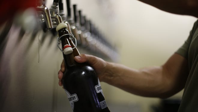 Owner Mike Mike Carbonelle fills a 32-ounce bottle with beer at Growler Country on Wednesday, May 13, 2015.