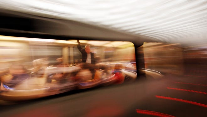 A rider holds on as a Metro train arrives in the Gallery Place-Chinatown Metro station Tuesday, March 15, 2016 in Washington. The head of the rail system that serves the nation's capital and its Virginia and Maryland suburbs says the system will shut down for a full day after a fire near one of the system's tunnels. (AP Photo/Alex Brandon)
