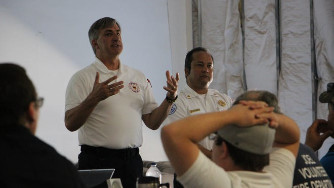 Mike Ristom (left), EMS chief, talks at an oilfield emergency workshop with Rick Lopez (right), Carlsbad fire chief.