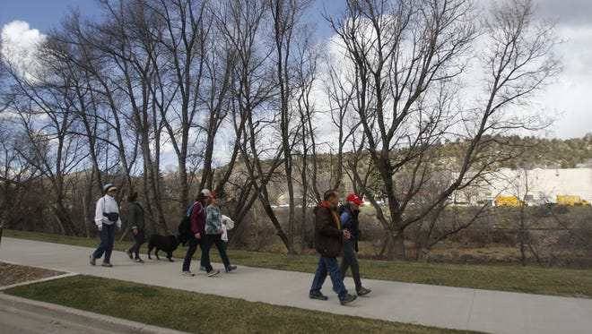 """Participants in a Live by Living """"Walk Along the River"""" event stroll along the Animas River Trail in Durango, Colo., on March 25."""