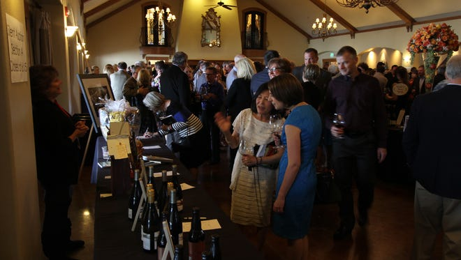Guests browse the silent auction during the Uncorked fundraiser for Family Building Blocks at Zenith Vineyards last year.