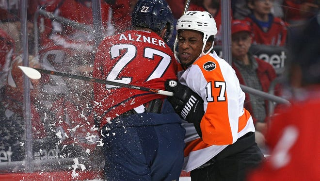 Wayne Simmonds checks Karl Alzner during the first period in Game 1.
